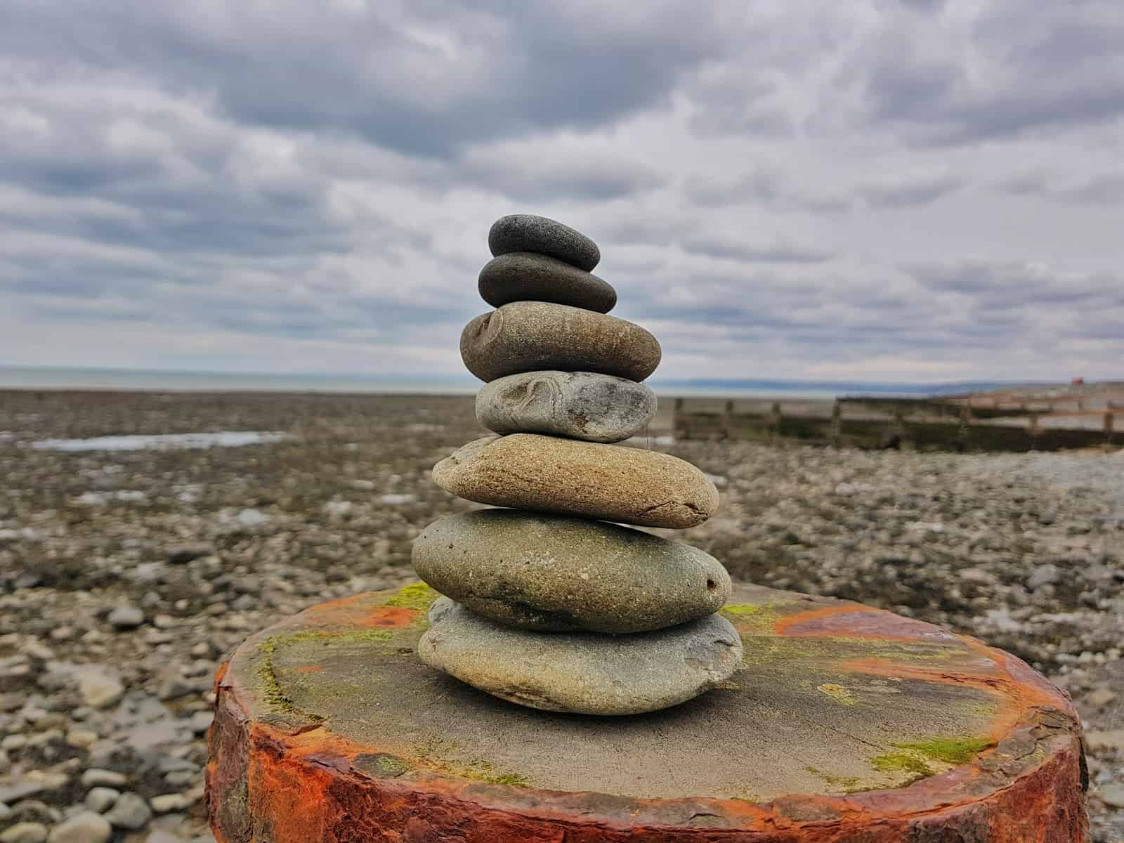 Small stone tower in foreground with Aberaeron pebble beach in background and cloudy sky