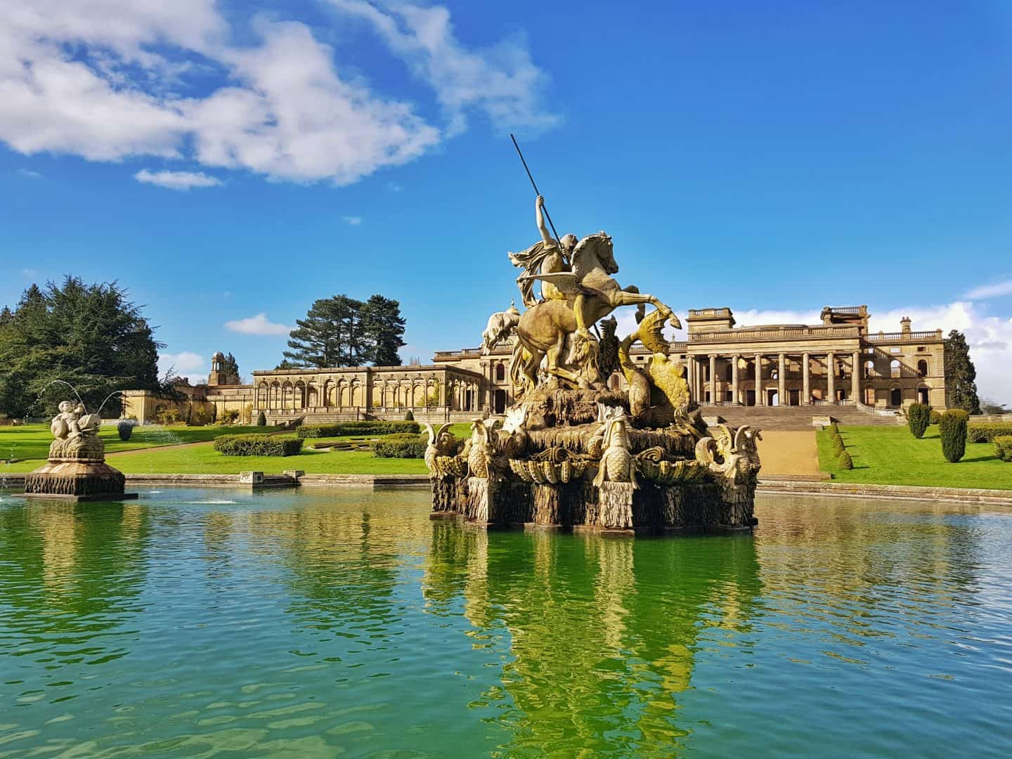 pond and fountain with Witley Court in background and blue sky