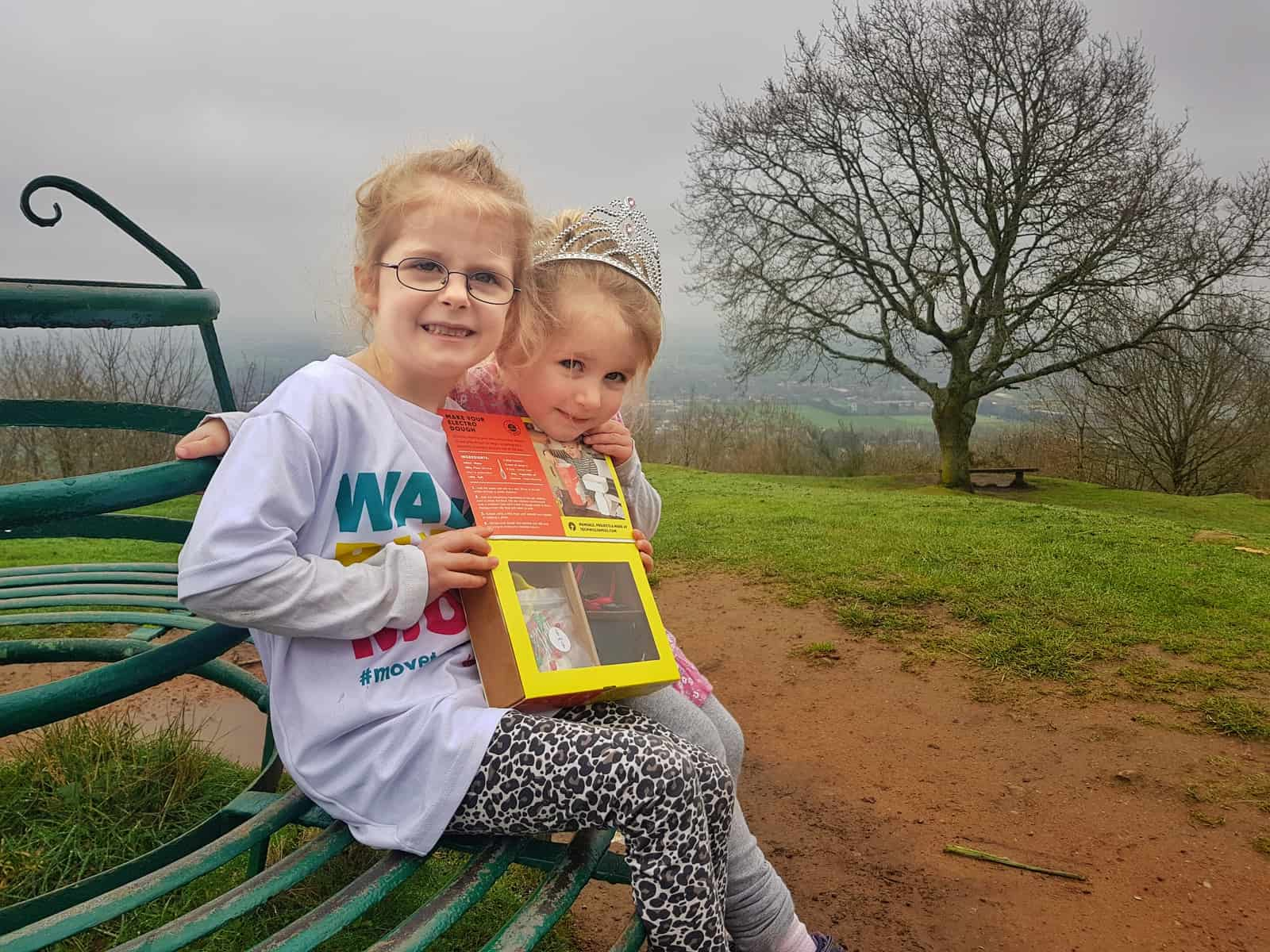 Two little girls sat on a bench holding an Electro Dough STEM science kit