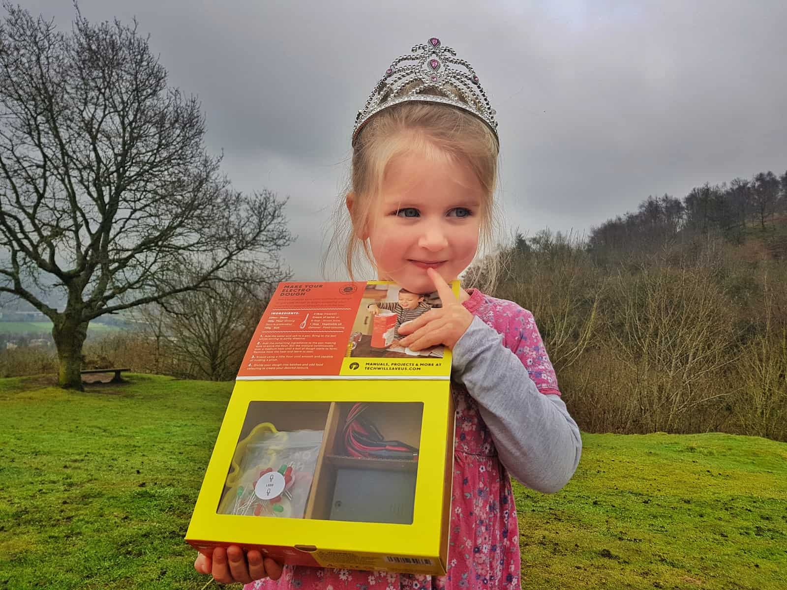 Little girl in tiara and pink dress holding an Electro Dough STEM science kit