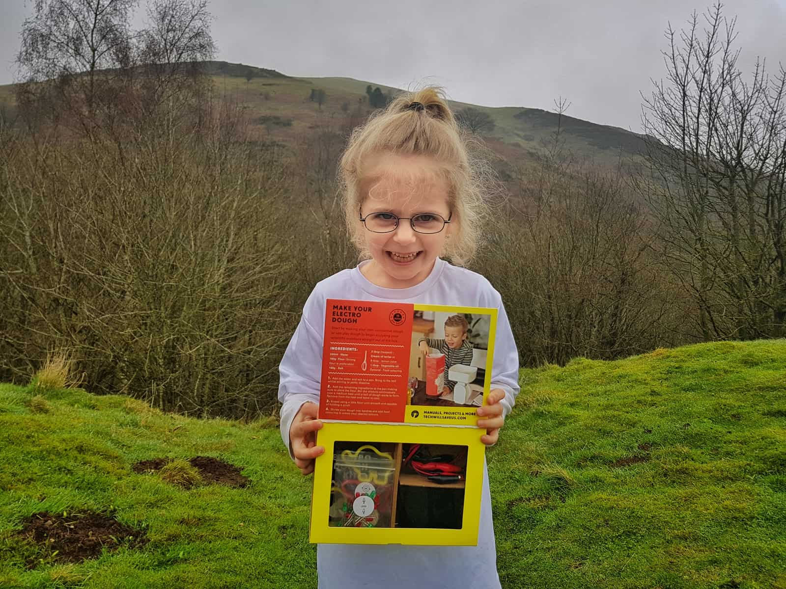 Little girl holding an Electro Dough STEM science kit with hills in background