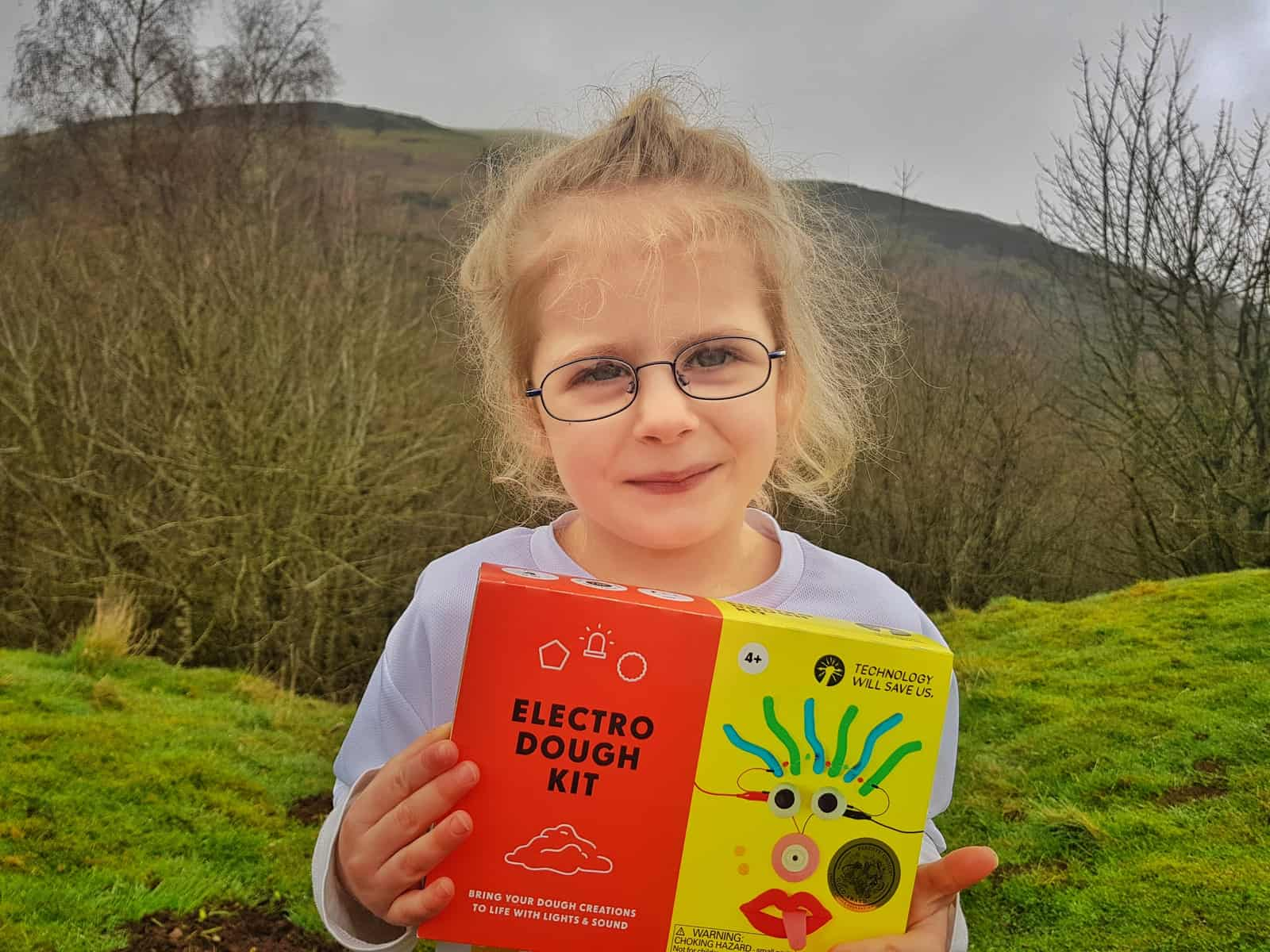 Little girl holding an Electro Dough STEM science kit