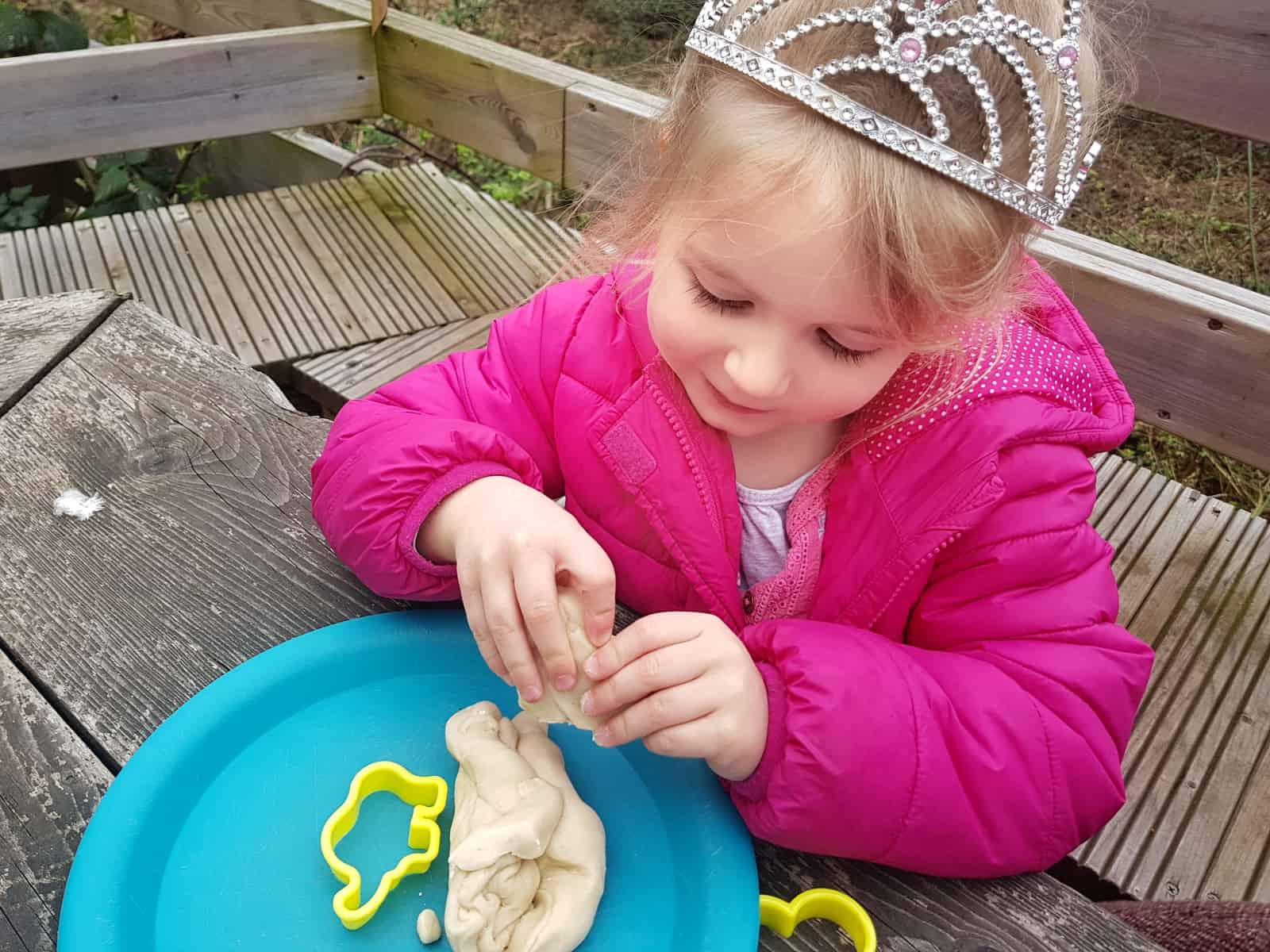 Little girl in pink coat and tiara creating a circuit from play dough with STEM science kit