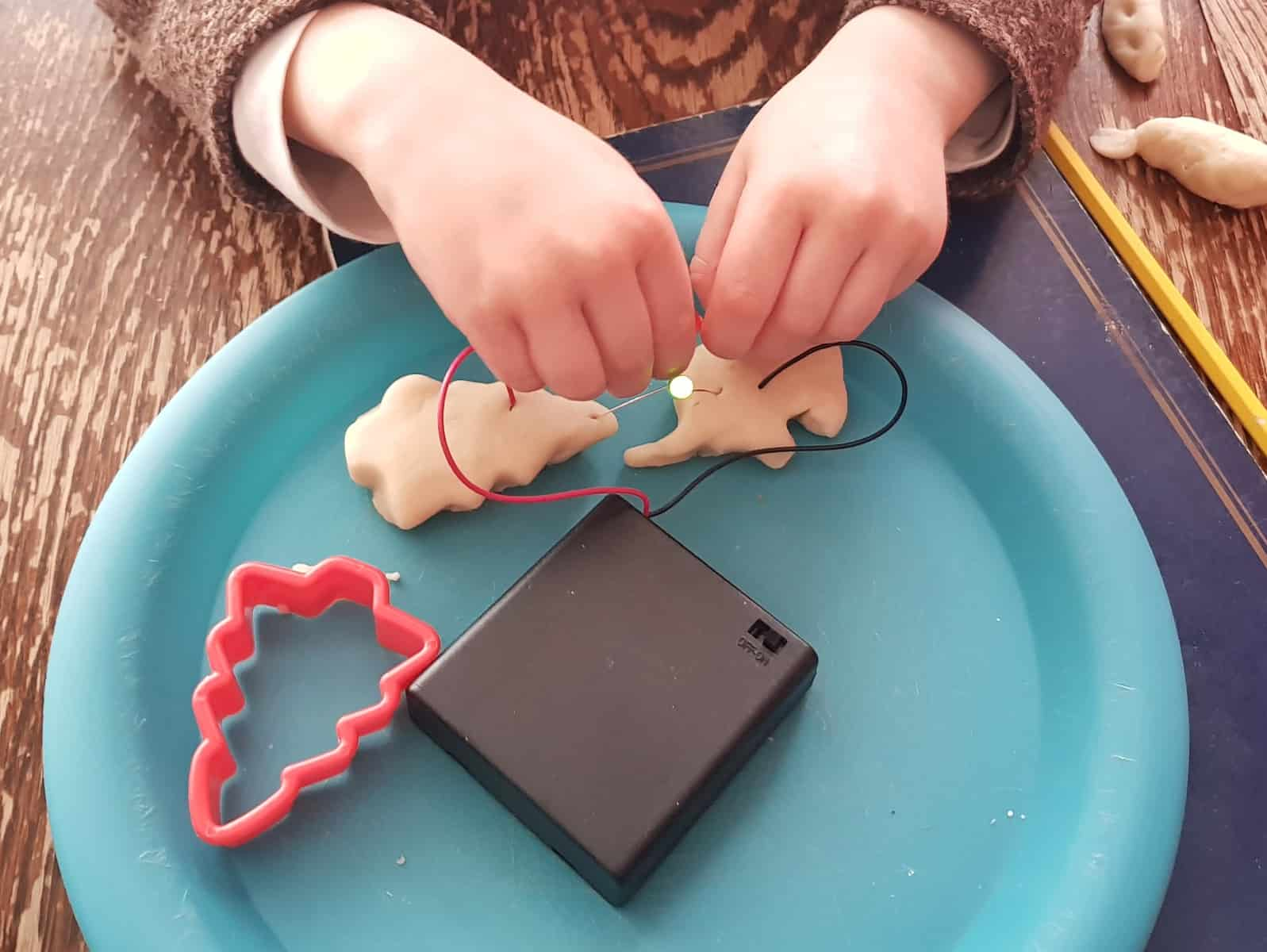 Little girls hands creating a circuit from play dough elephant and tree with STEM science kit