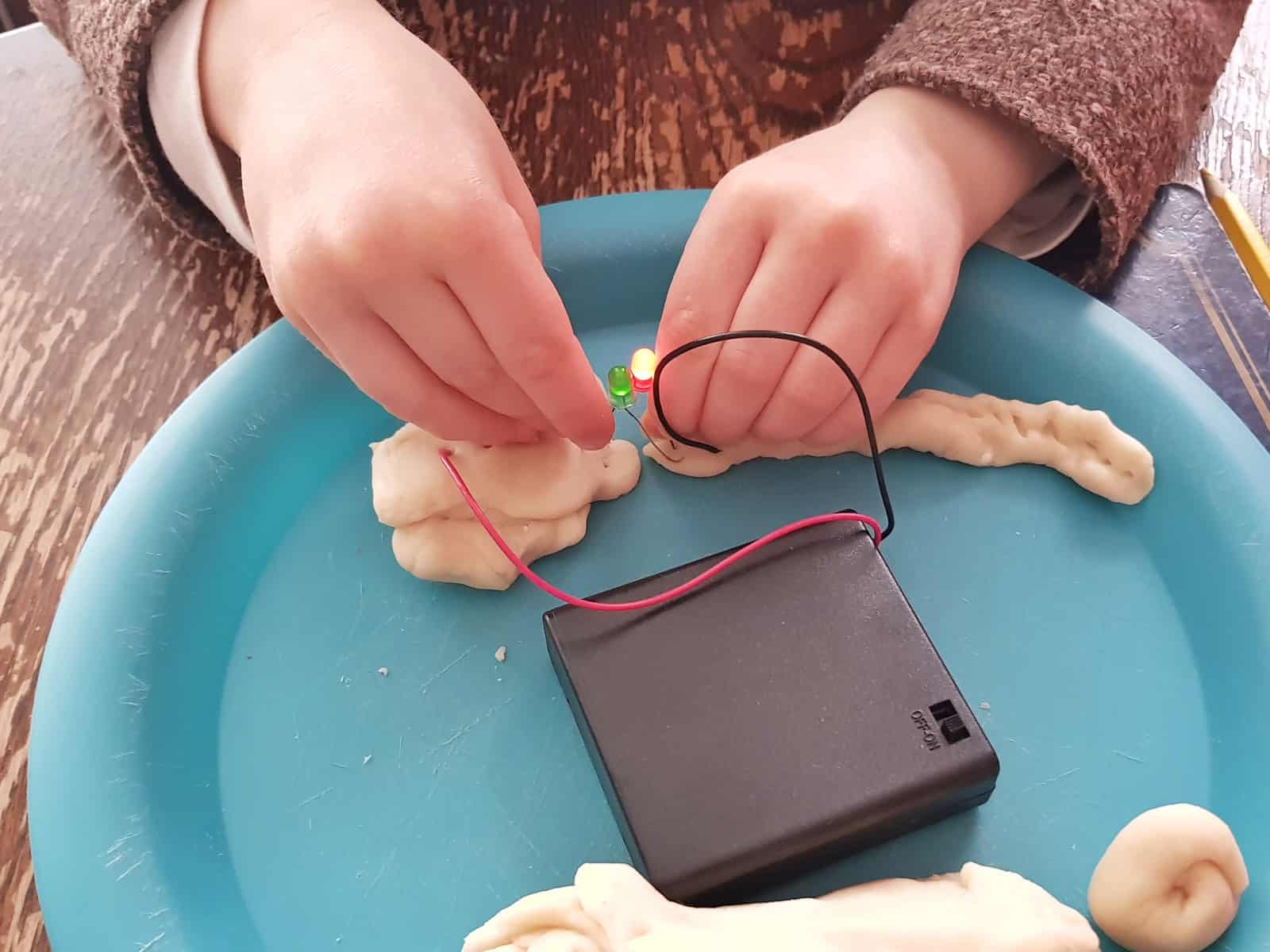 Little girl's hands creating a circuit from play dough with STEM science kit