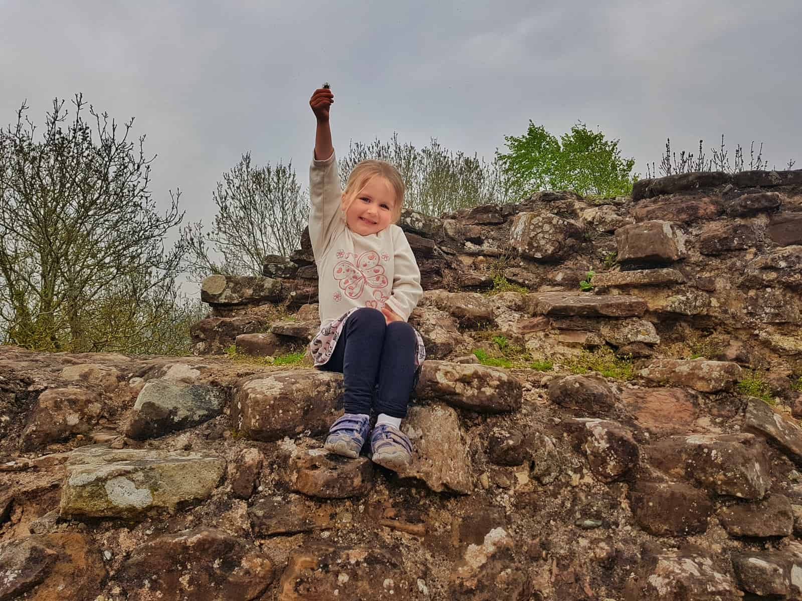 little girl sat on a wall at Goodrich Castle