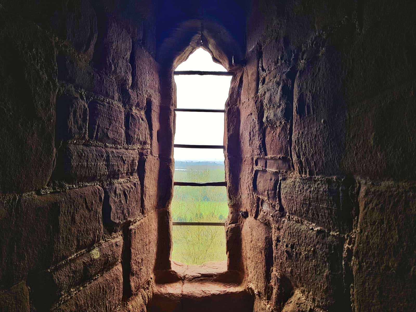 murder hole window at Goodrich Castle with countryside beyond