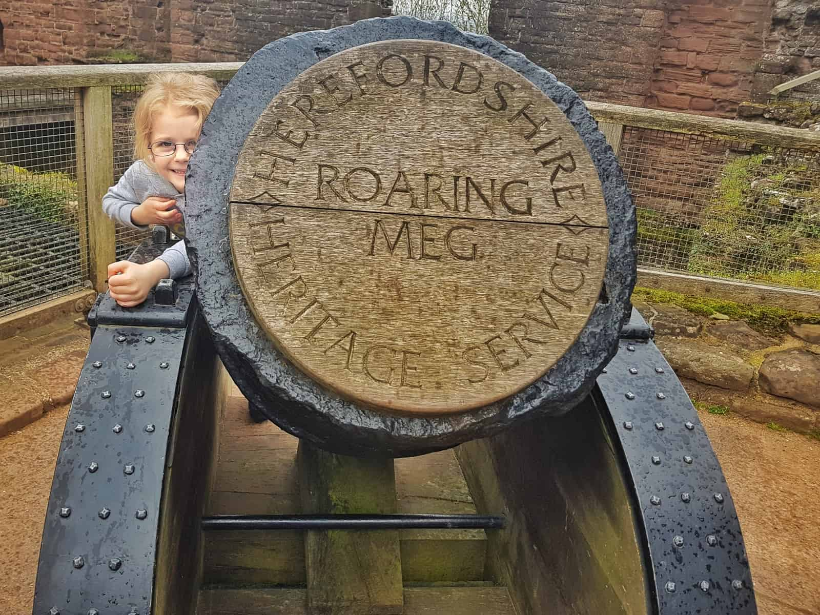 Little girl peeping out from behind roaring meg at Goodrich Castle