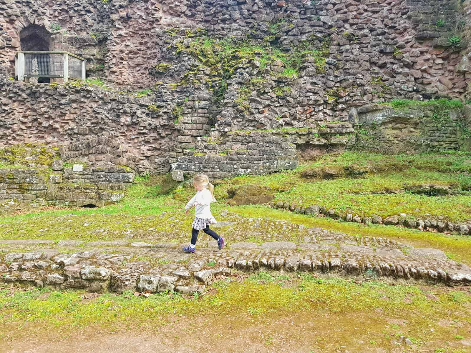 Little girl running through ruins of stables at Goodrich Castle