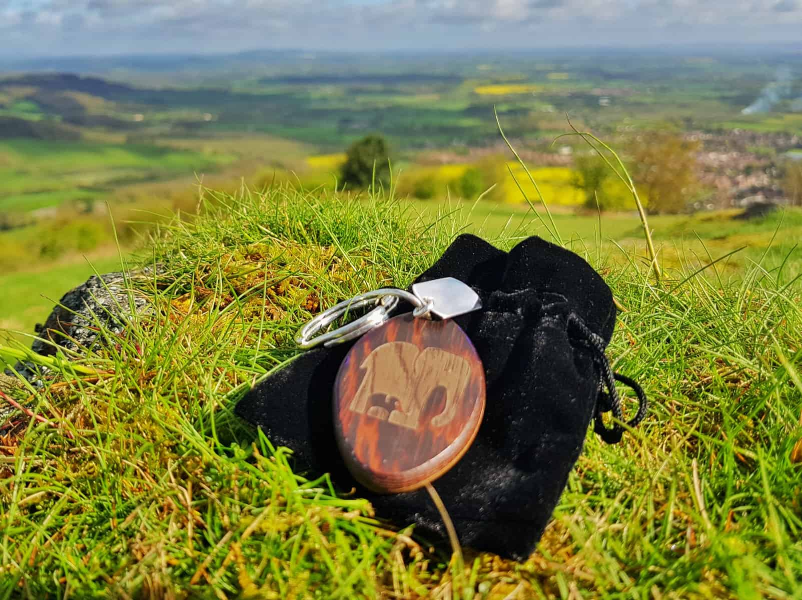 wooden keyring on black velvet bag, backdrop hillside