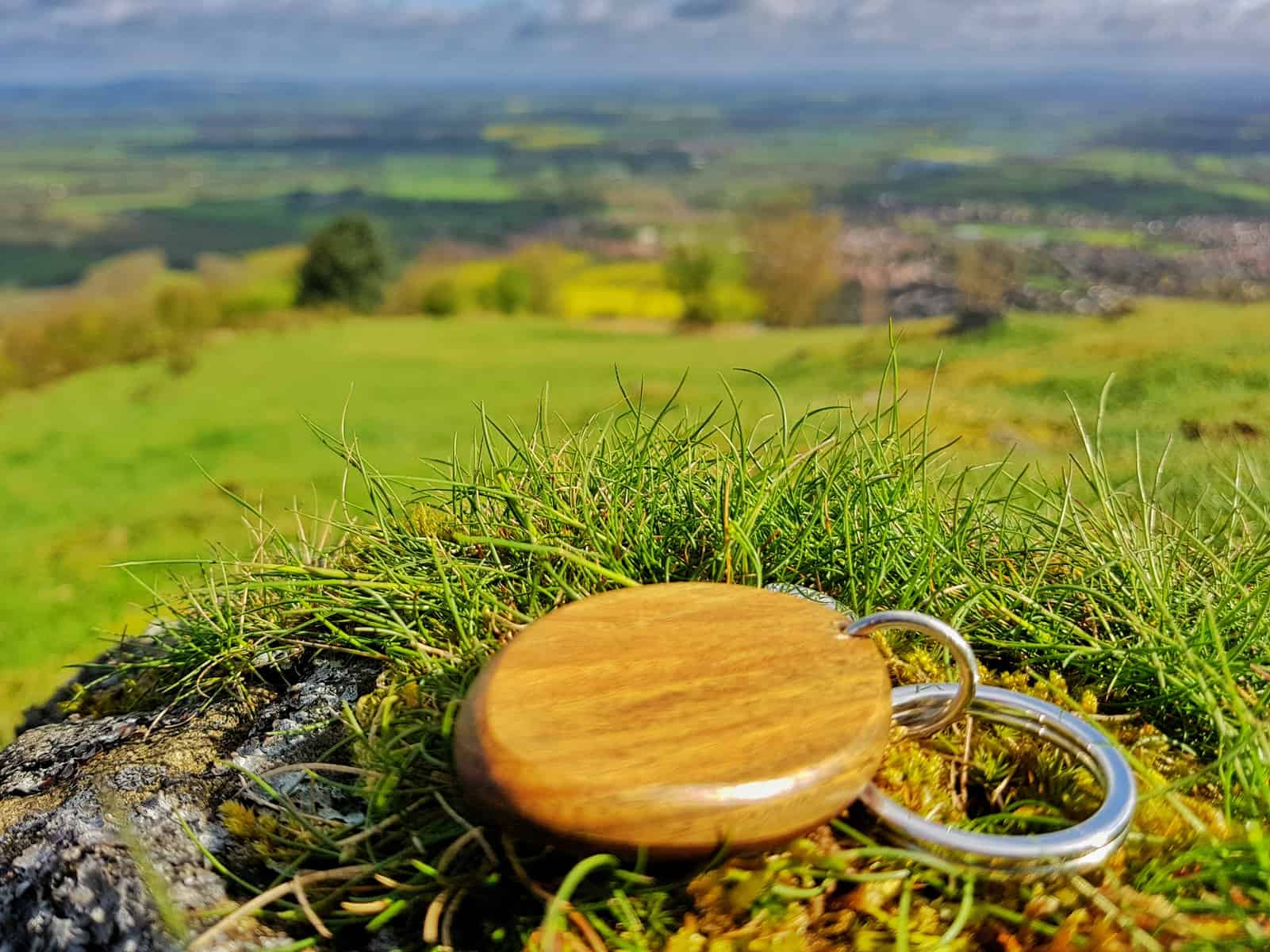 wooden keyring with backdrop of hillside
