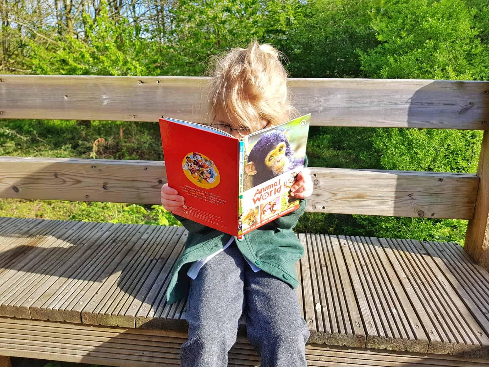 Girl reading Disney Animal World book