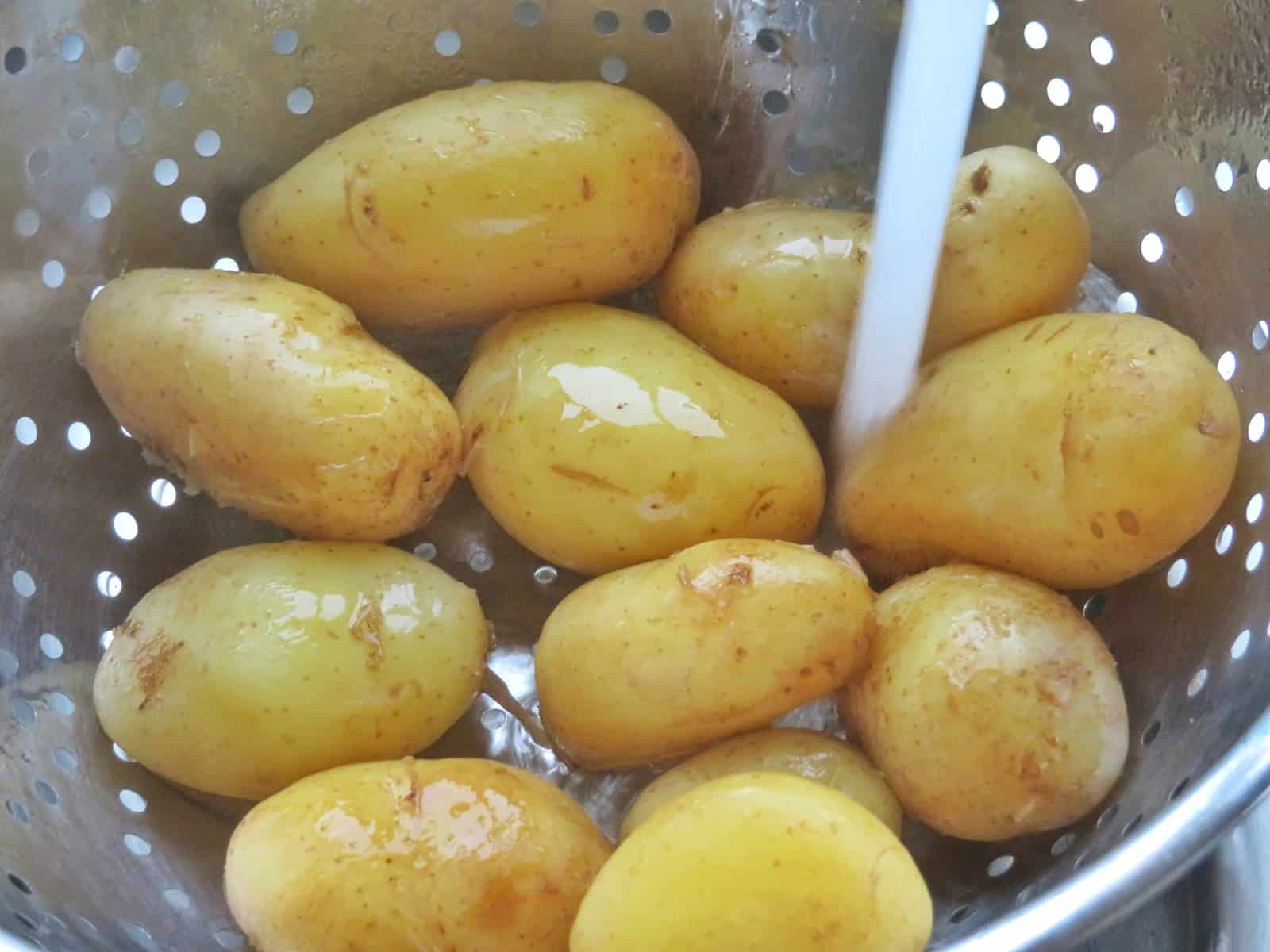 Jersey Royal potatoes under a tap