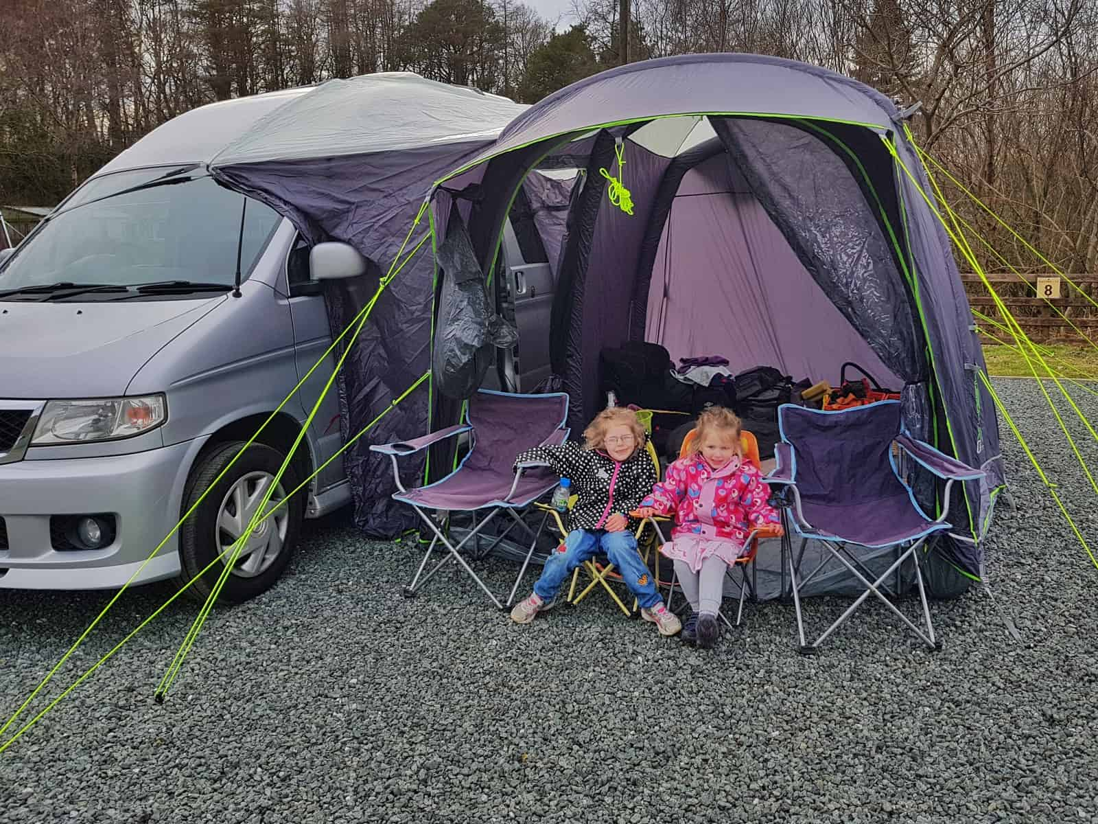 Camper van with driveaway awning attached and two little girls sitting outside on chairs