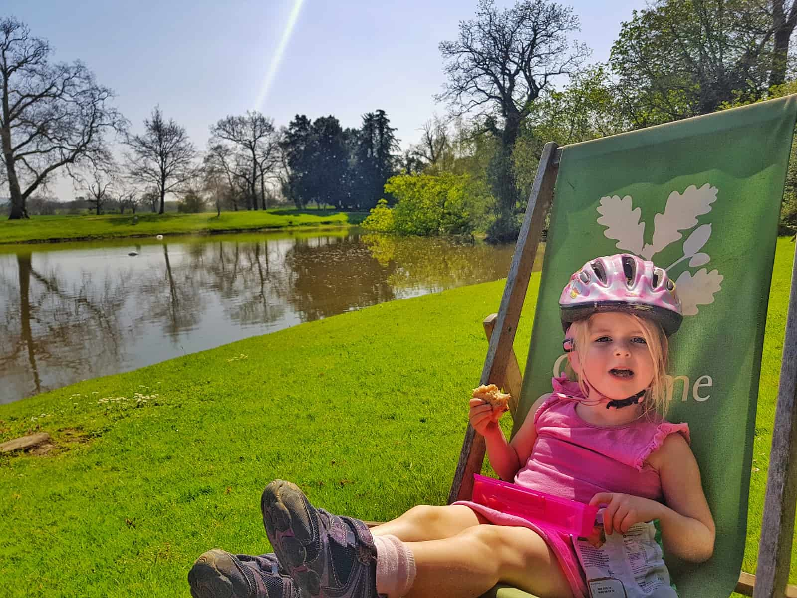 Little girl sitting on a green deck chair by a lake eating a sandwich whilst wearing a pink cycle helmet.