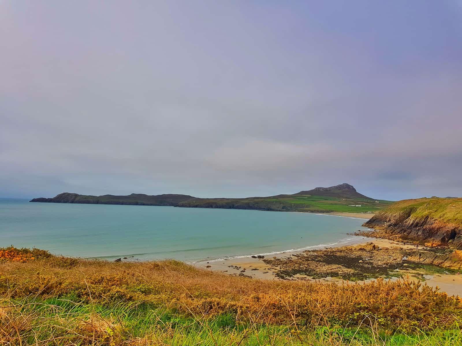 A view of blue sea and Porthsele, a Pembrokeshire open water swimming beach near Pencarnan farm campsite