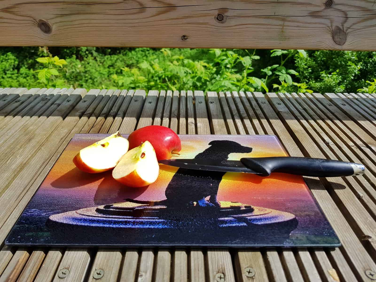 apple on chopping board with a photo of a dog against a sunset