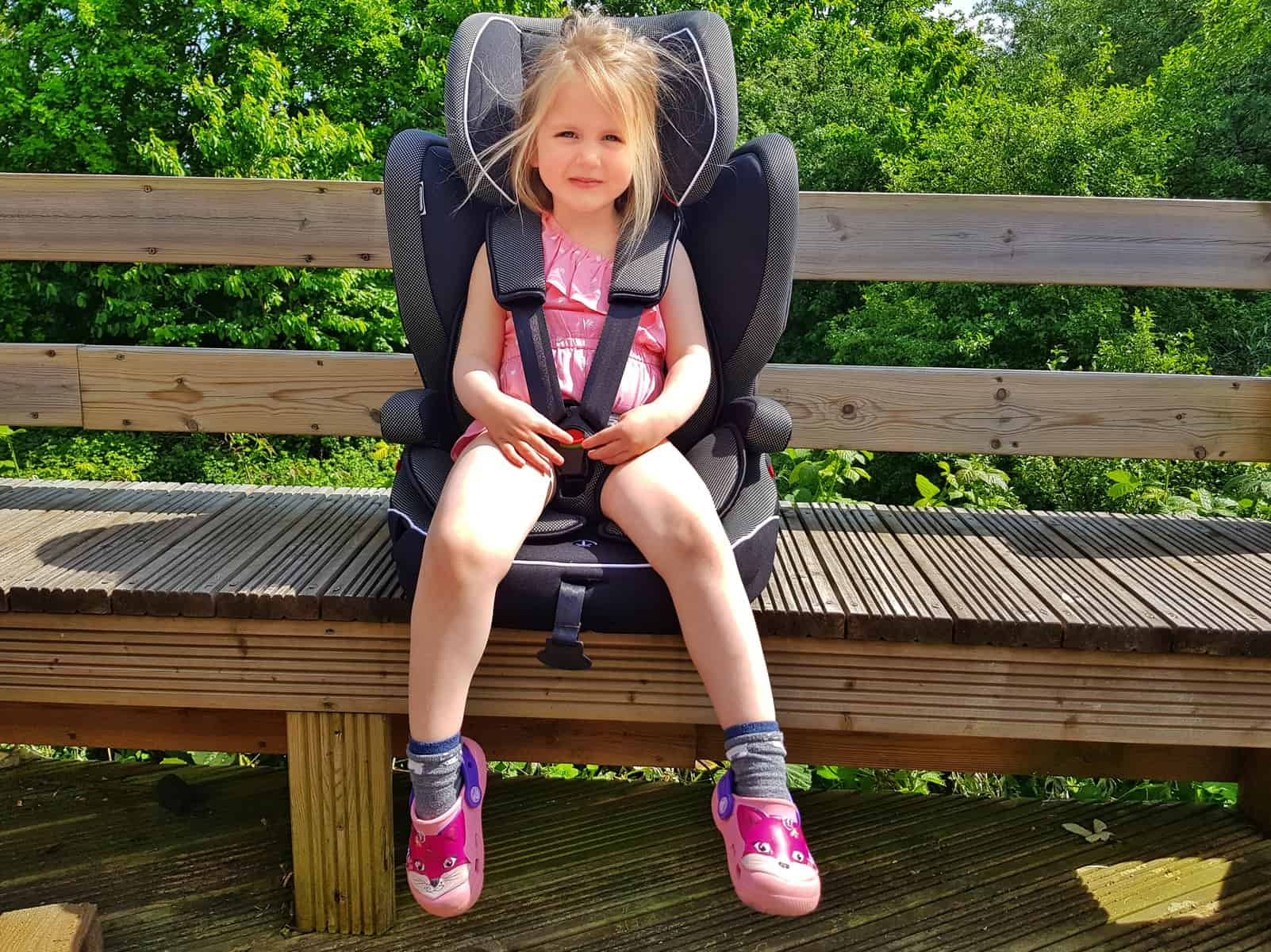 Little girl in pink outfit sat in car seat with five point harness, seat rests on a bench outside