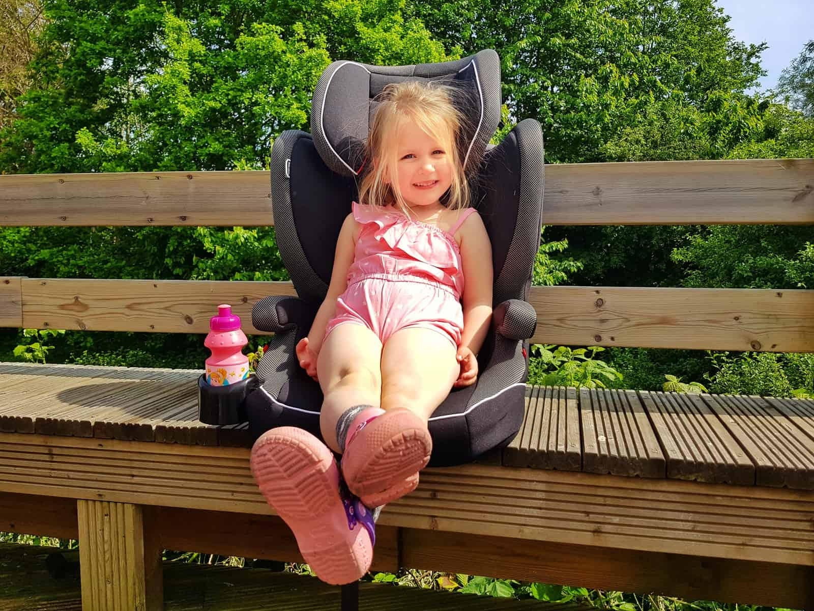 Little girl in pink outfit sat in car seat on a bench outside with drink in drink holder beside her