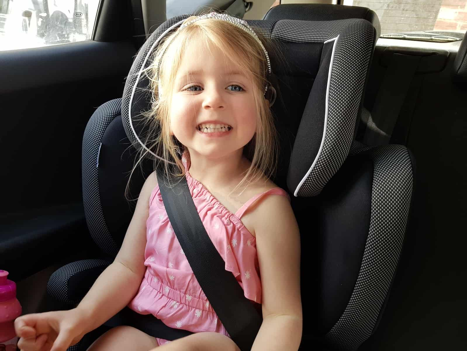 Little girl in pink outfit sat in car seat smiling