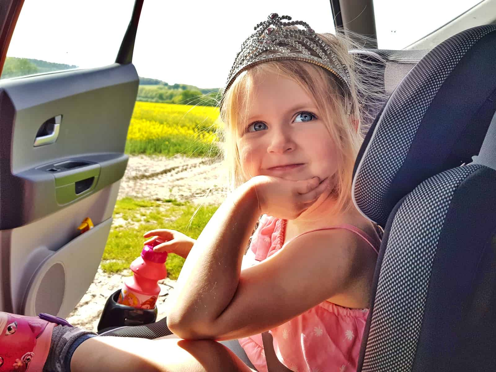 Little girl in pink outfit and tiara sat in car seat with hand on chin, car door open onto a field of oilseed rape