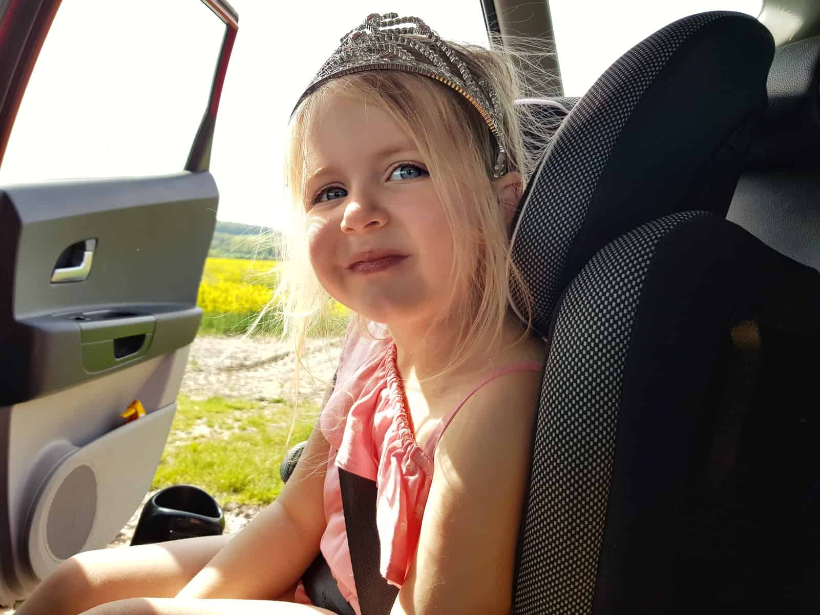 Little girl in pink outfit and tiara sat in car seat, car door open onto a field of oilseed rape