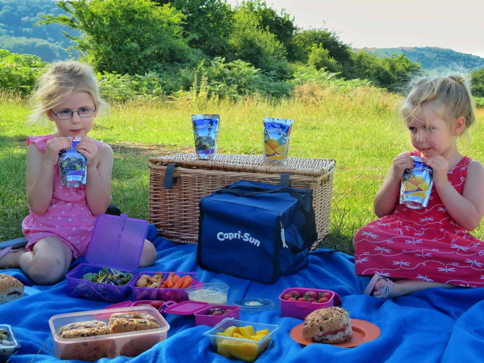 Two girls on a picnic blanket with Capri-Sun drinks and Capri-Sun cool bag with grass and hills behind