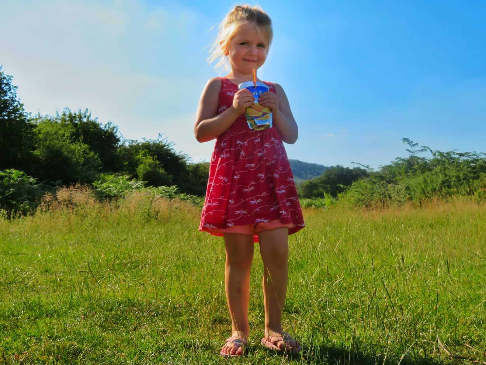 Little girl stood on grass drinking Capri-Sun with blue sky behind
