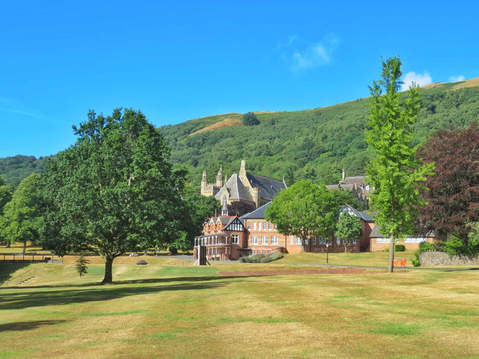 Super Camps Malvern College buildings set on lawn at foot of green hills