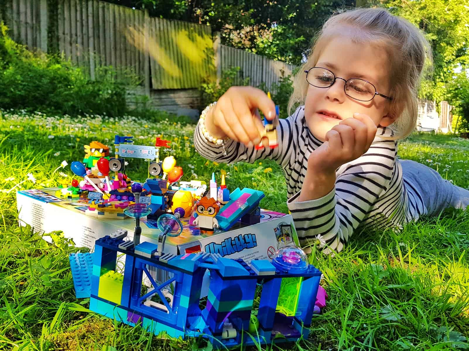 Little girl building a lego model in the garden - one of 100 ideas for summer holiday activities to beat boredom