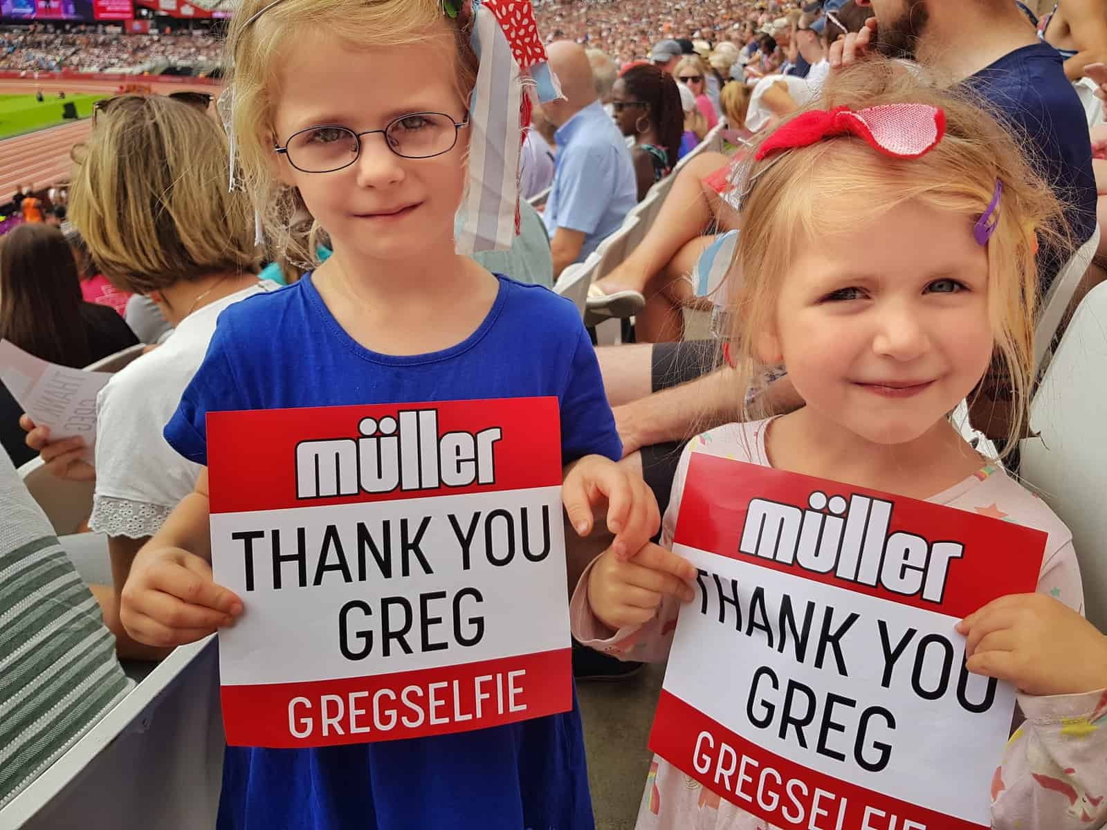 Two girls holding Thank you Greg signs at the Muller Anniversary Games