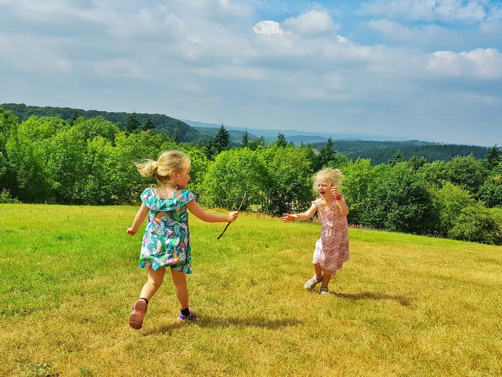 Two little girls passing a stick practicing their relay races after watching the Muller Anniversary Games
