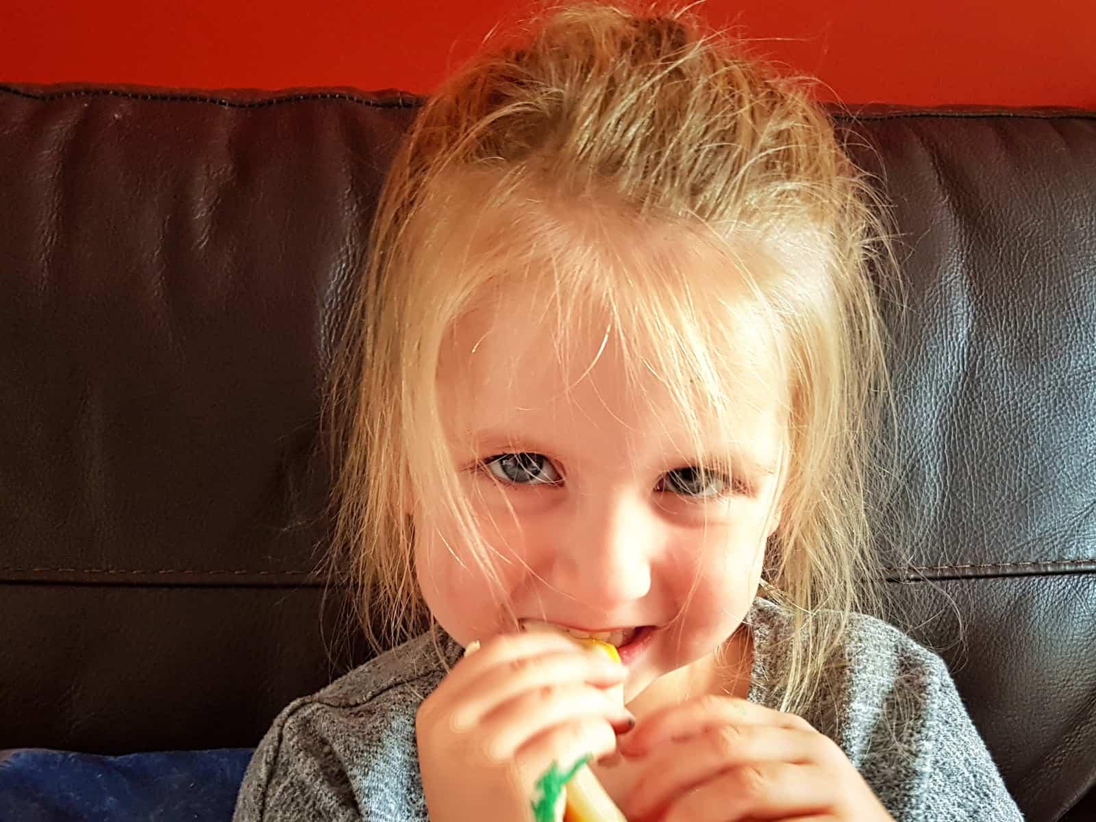 Pik-Nik cheese sticks girl eating indoors
