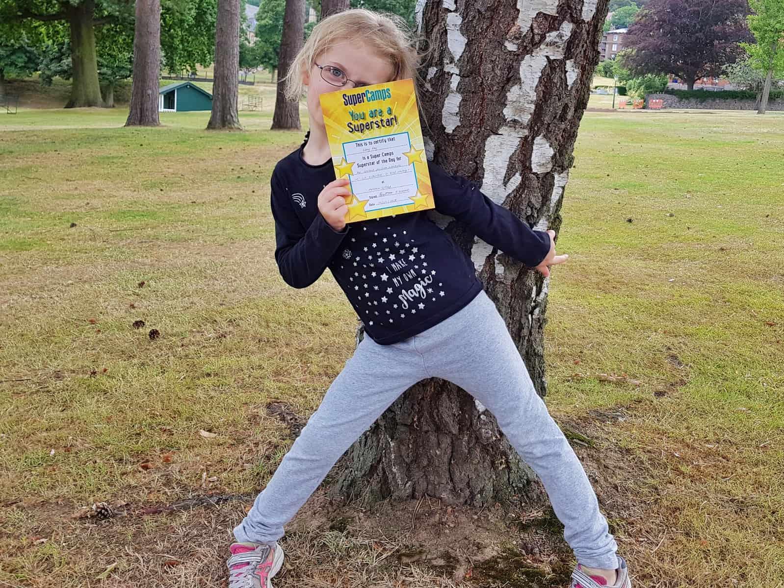 Super Camps Malvern College little girl holding a certificate