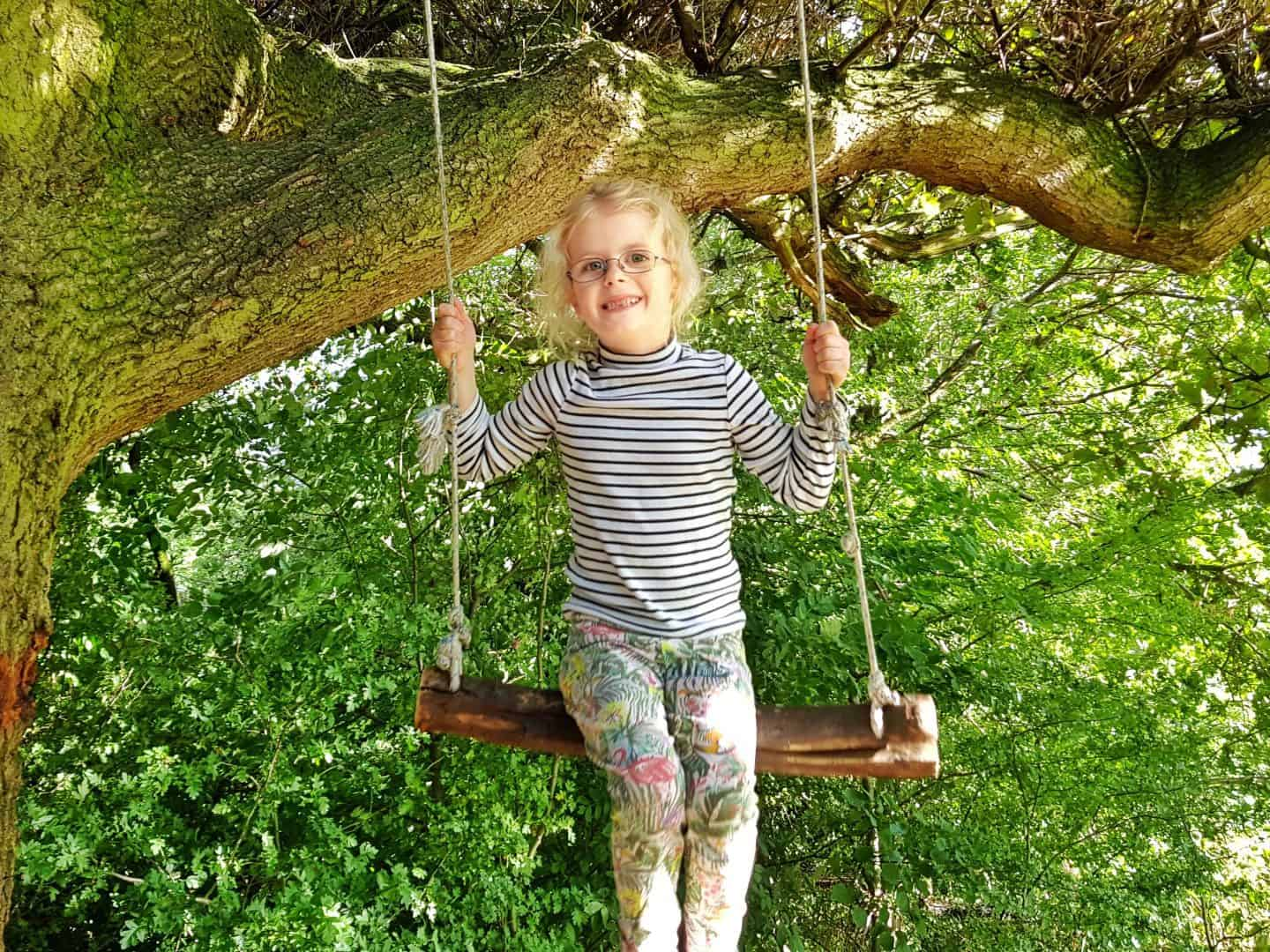 10 tips to prepare your child for tooth extraction girl on a swing before extraction