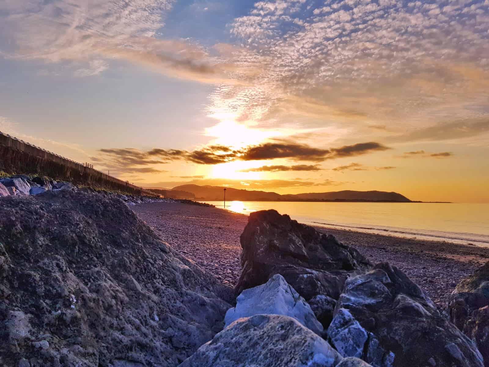 Hoburne Blue Anchor rocks on beach at sunset