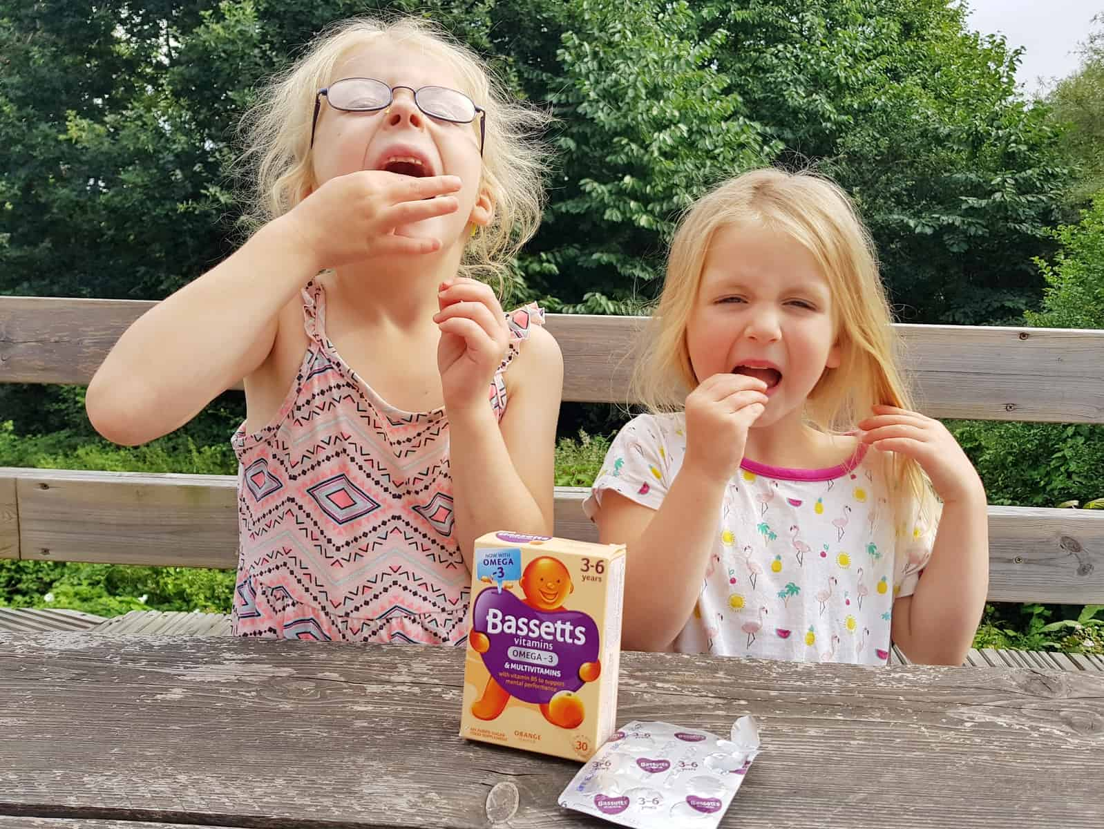 two girls eating bassetts vitamins