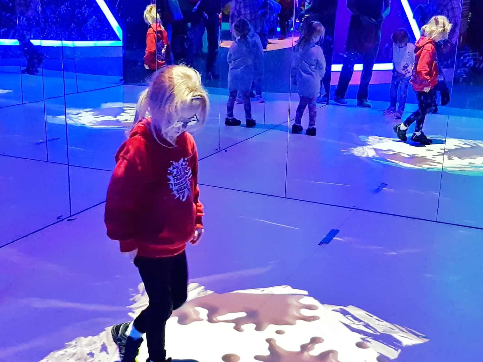 A family day out at Cadbury World Birmingham little girl playing in mirror game