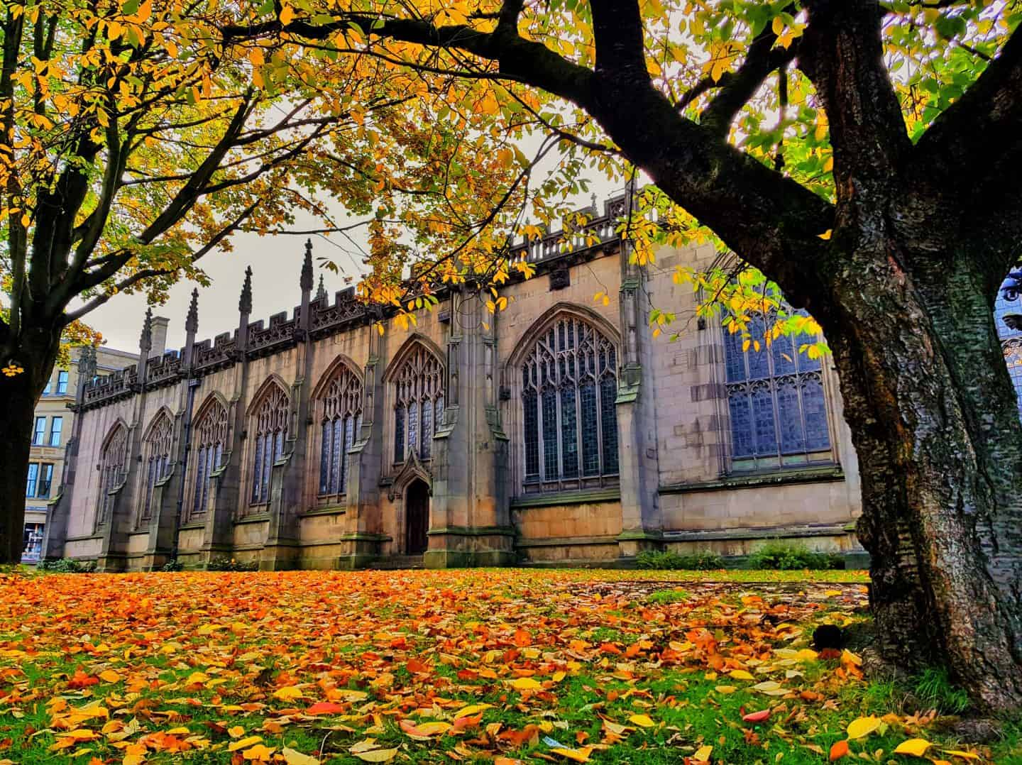 Manchester Cathedral in autumn with leaves in the foreground