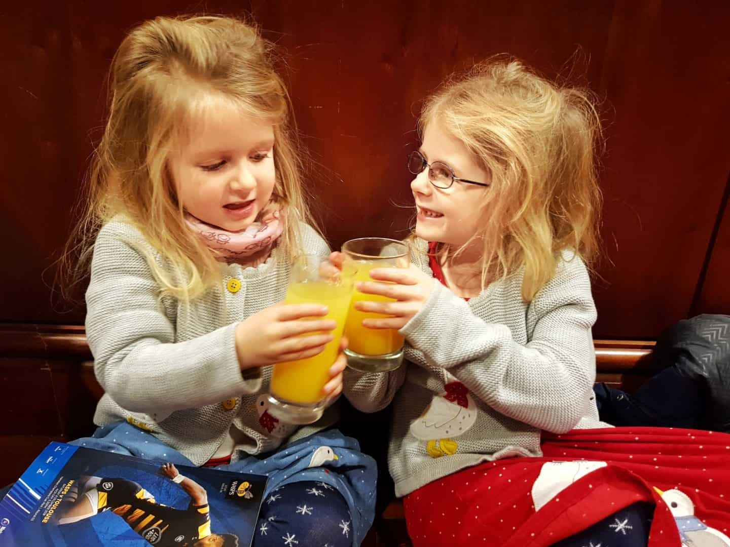 Close friends are overrated two little girls knocking their orange juice glasses together