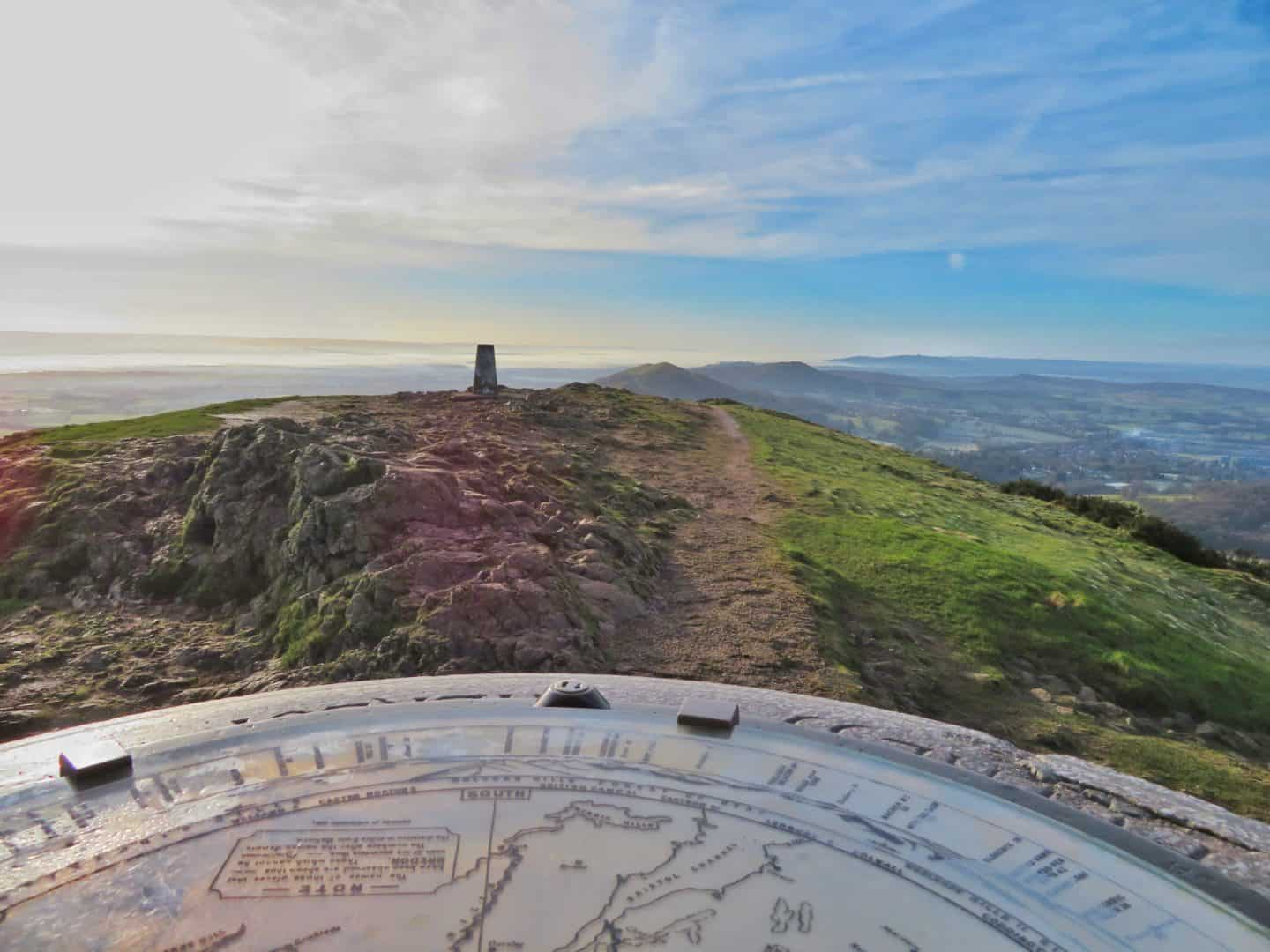Direction stone in the foreground with a view along the Malvern Hills from the Worcestershire Beacon in the background