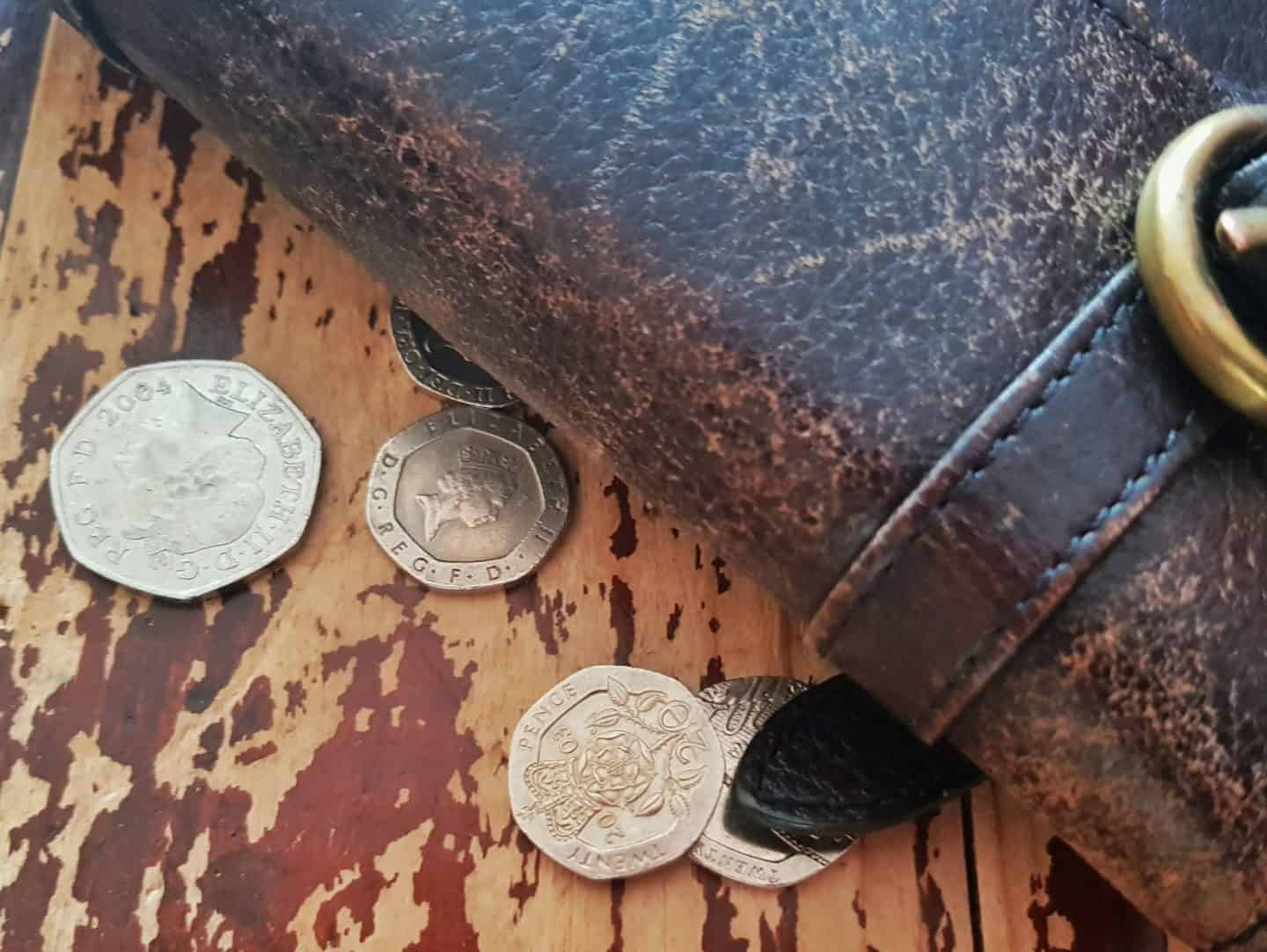purse with money in the form of coins beside it