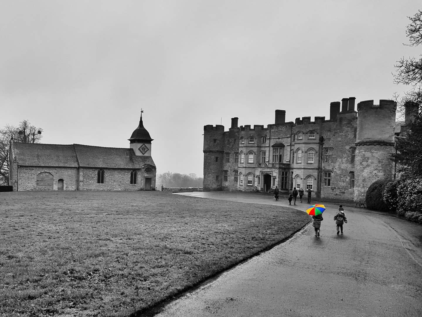 Croft Castle National Trust Herefordshire in black and white with children walking towards it holding rainbow umbrella