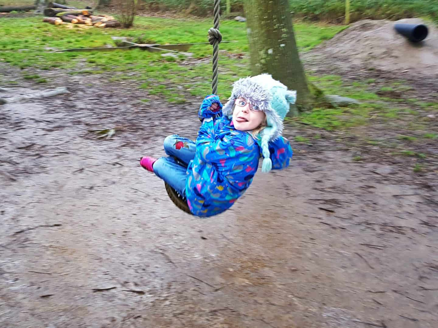 National Trust membership little girl in a blue coat on a rope swing