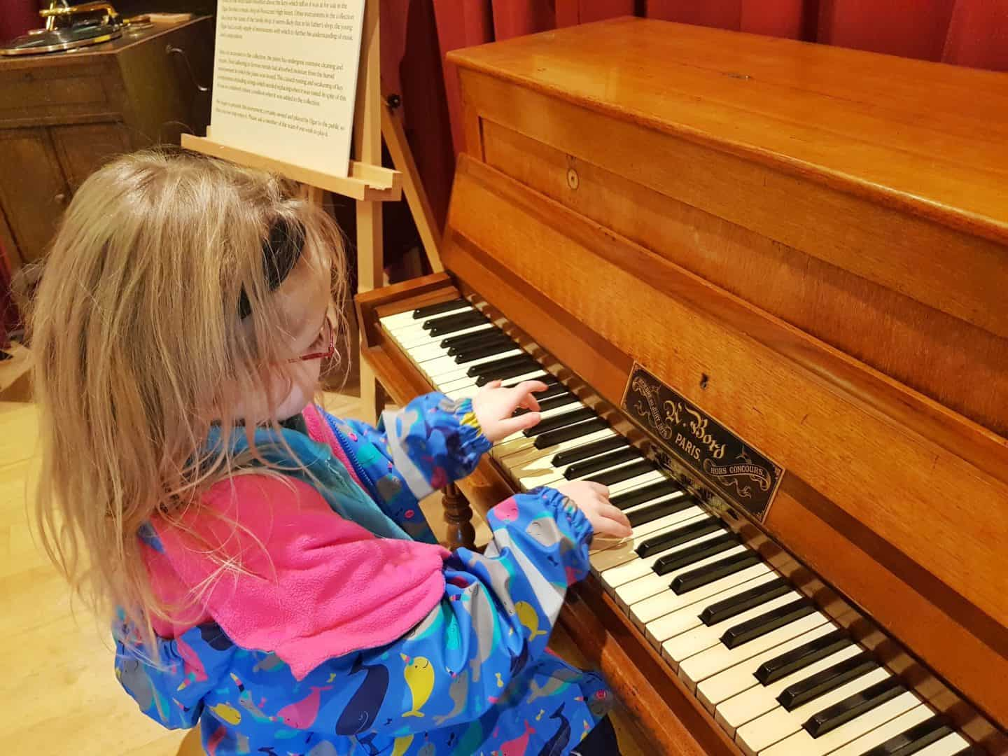 The Firs National Trust in Worcestershire girl playing piano