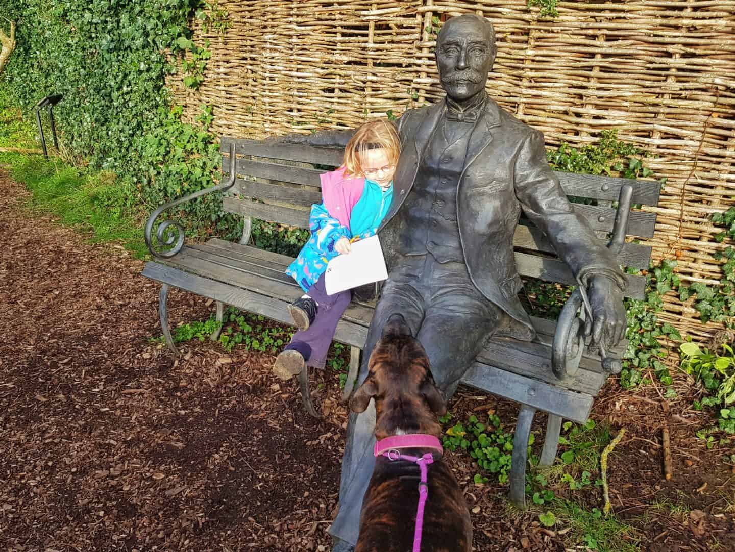 The Firs National Trust in Worcestershire girl sat on bench with statue of Elgar as dog looks on