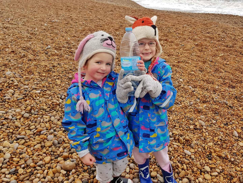 Children on beach holding plastic bottle picked up as litter