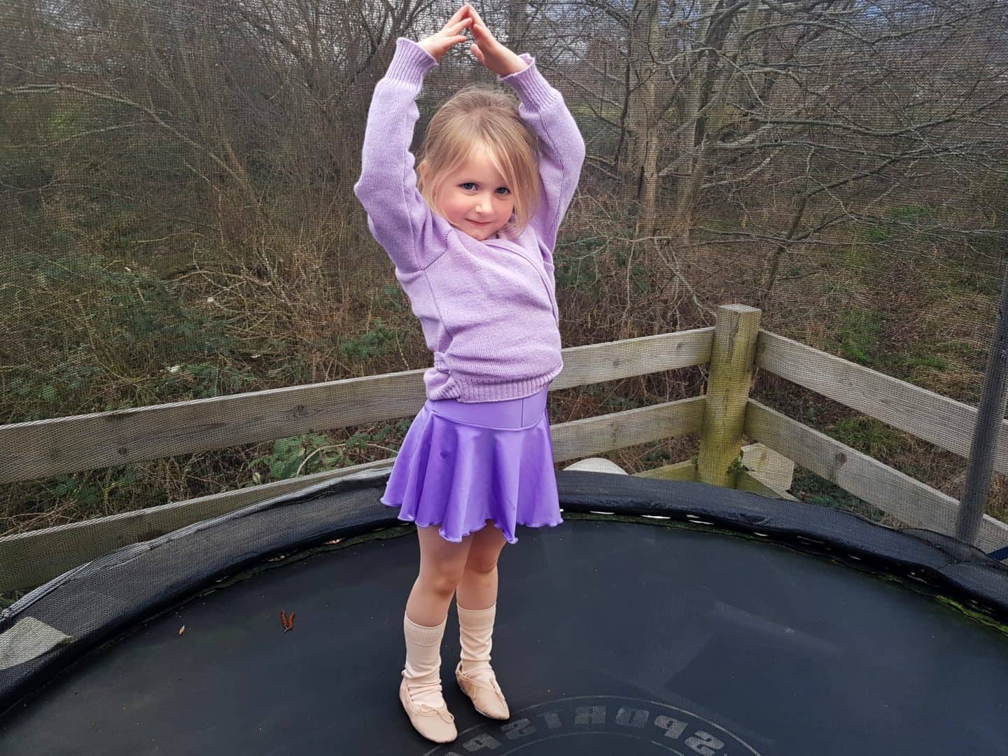Dance Gear review girl in purple ballet leotard and cardigan on trampoline