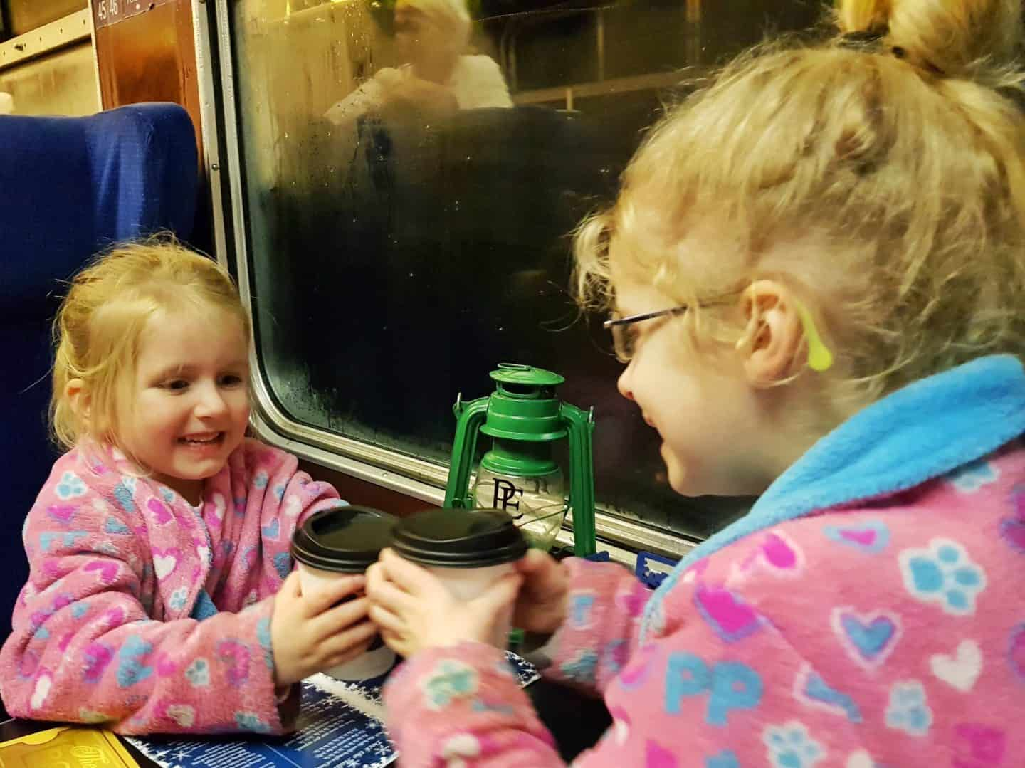 Girls in dressing gowns on train toasting with hot chocolate