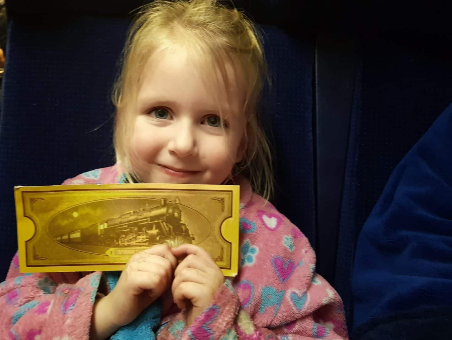 Polar Express Telford girl in dressing gown holding golden ticket